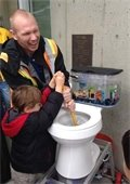 Man and child plunging a toilet