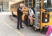Police Captain greets kid leaving bus
