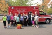 Seniors with firefighters and aid car