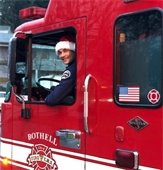 Firefighter in Santa hat in fire engine