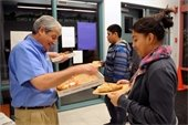 Man serving pizza to junior high students