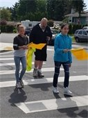 Two children crossing at a crosswalk holding a flag.