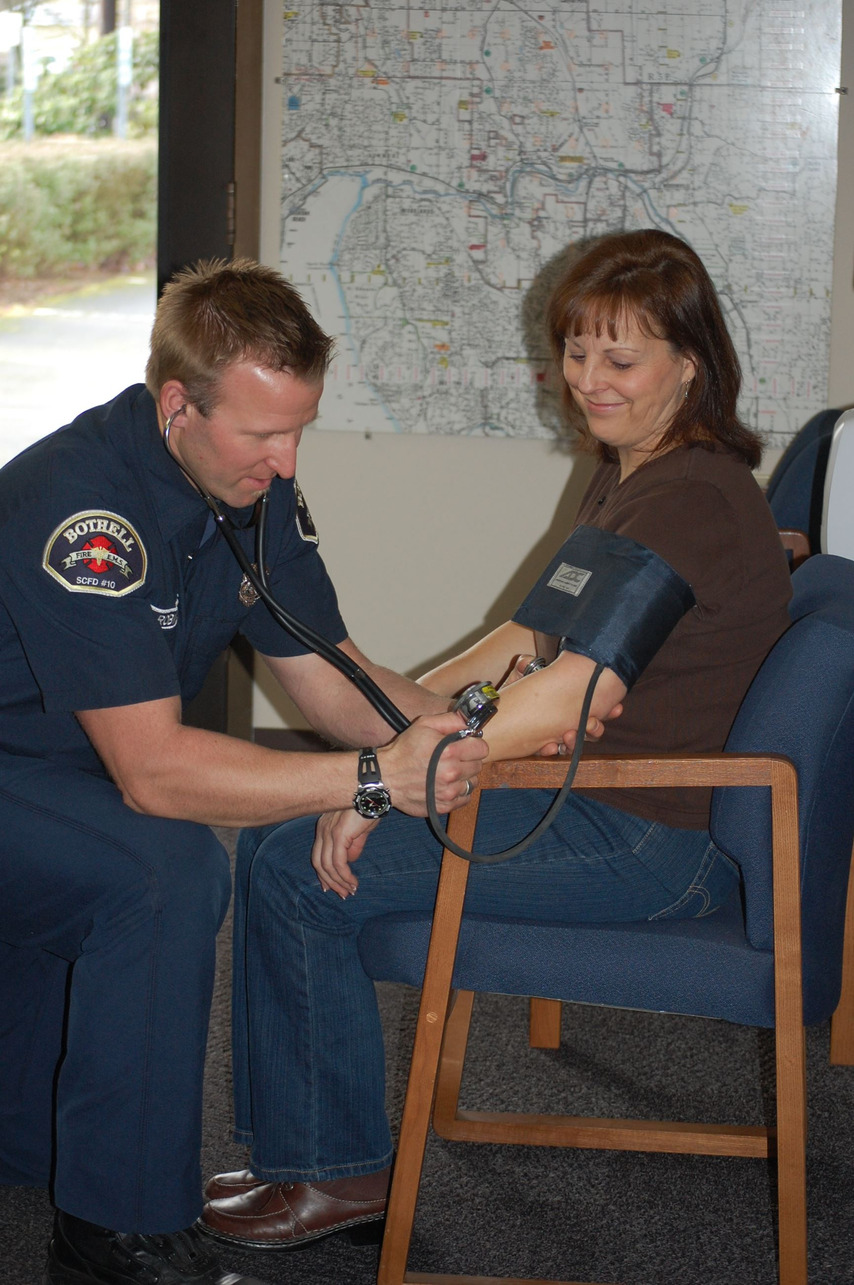Fire Department member performing a blood pressure check on a woman.