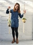 woman holding two plant hangers